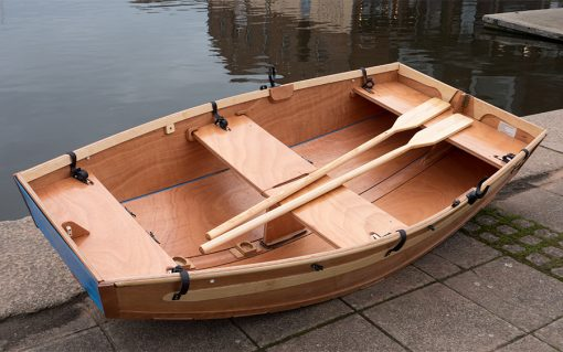 Beautiful seahopper folding rowing boat made of wood with oars across the seats