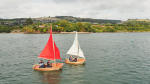Beautiful wooden Seahopper folding boats sailing on the River Teign - red sails and white sails on show