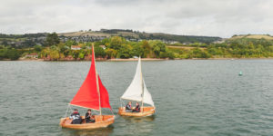 Beautiful wooden folding boats sailing on the River Teign - red sails and white sails on show