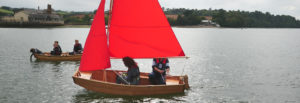 side view of seahopper folding sail boat with red sails