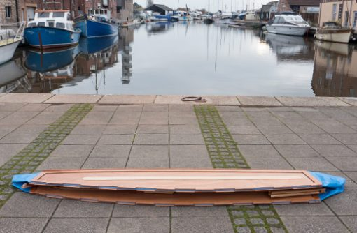 beautiful wooden seahopper boat folded flat with blue ends on the Quay, Exeter