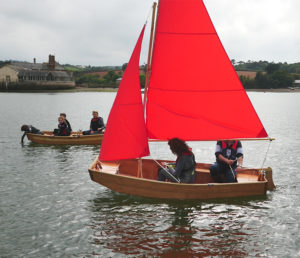 side view of seahopper folding boats motor and sail with beautiful red sails