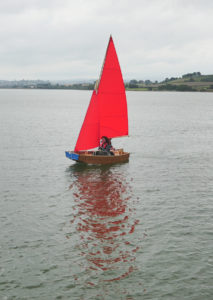 seahopper folding boat with red sail and beautiful reflection on the River Teign