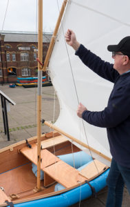 seahopper wooden folding sail boat raising the white sail on The Quay, Exeter