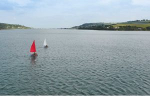 seahopper portable sail boats on the River Teign - one with red sails, the other with white