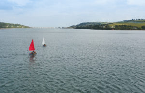 River Teign with beautiful wooden Seahopper boats sailing - one with red sails, the other with white sails